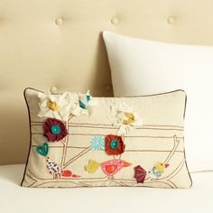 Appliqued flowers and birds make their home on this charming decorative pillow from Cottage Home. A rectangular shape and zipper cover closure highlight this pillow.