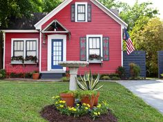 After: Red, White and Blue  The house gets an Americana-themed makeover complete with bold red paint and custom-made metal shutters with star-shaped cutouts. The porch is sheltered from the sun with a corrugated tin awning, and a red butterfly-shaped bench and birdbath dress up the landscaping. Dark blue paint on the window trim completes the schoolhouse look.