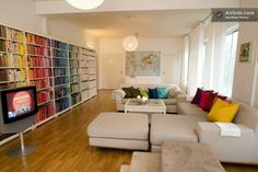 A neutral room in Sweden turned incredible with color coded books and matching throw pillows.