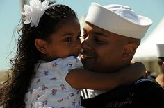 A Sailor stationed aboard the guided-missile destroyer USS Porter (DDG 78) embrace a family member after arriving at Naval Station Rota, Spain.