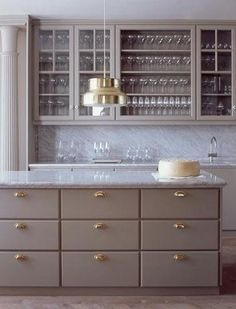 gray kitchen cabinets with glass fronts and brass accents  (michael graydon)