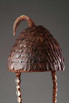 Lega Peoples Ceremonial Headdress (1900 to 2000) - Pangolin, fibre, shells These ceremonial hats were regarded by the Lega as sacred objects and were only worn by high-ranking initiates of the Lega Bwami society. Demonstrating the status of its owner, the headdress was used in dances to carry an important symbolic message. To the Lega the pangolin is a cultural hero who, they believe, taught them how to roof their houses...similar to that of its bony scaly carapace...