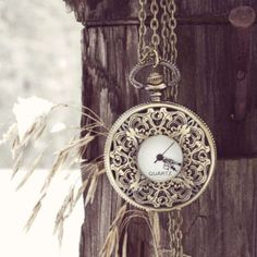 Sweet carved lace details adorn this antiqued gold toned pocketwatch necklace. Hangs beautifully below the bust and is sure to keep you stylishly on time.