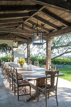 Antique Mexican Street Lanterns with Bird motif hang above the rustic farm table in this outdoor dining area in Bel Air.