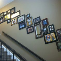 Stairwell picture collage of family and friends- tip is to lay it out on the floor first using a string as a straight line and figure out angle your frames should be on stringline