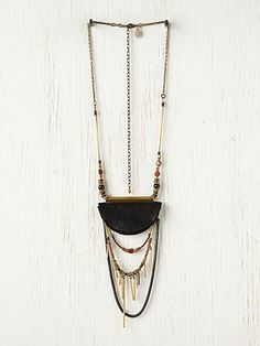 "Eclipse Necklace    Chain necklace with beading and layers of bead fringe with leather pendant.    *By Annie Costello Brown  *100% Leather, Solid Brass, Glass, Bloodstone  *Made in the USA  *19"" long  *3"" wide pendant"