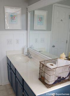 Boys bathroom makeover. Painted blue vanity, grey walls, board and batten, DIY art.