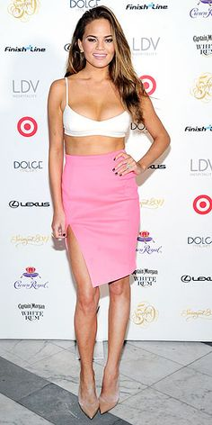 Last Night's Look: Love It or Leave It? | CHRISSY TEIGEN  | She just added Sports Illustrated cover star to her résumé, and now we think the supermodel should include a line about being a professional crop top wearer. She flaunts her toned bod in a midriff-baring design and a hot-pink side-slit skirt (both by Milly) at the magazine's swimsuit party in South Beach.