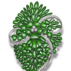 A jadeite and diamond brooch Set with intense green vari-shaped jadeite cabochons of very good translucency, decorated by brilliant-cut diamonds, to stylised ribbon motifs set with similarly-cut diamonds, mounted in 18k white gold, the diamonds estimated to weigh approximately 2.10 carats in total.