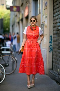 - Layer a pinafore midi dress of a head-turning hue with a white tee.