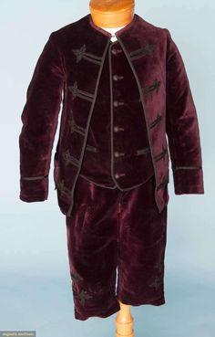 BOY'S THREE PIECE VELVET SUIT, 1880s  Deep plum 3-piece formal suit w/ black trims: open front jacket, collarless, 5 pair black braid trims, long button vest, 3 pockets, wave & stripe patterned cotton lining, breeches w/ braid trims, dot & stripe cotton lining, excellent.