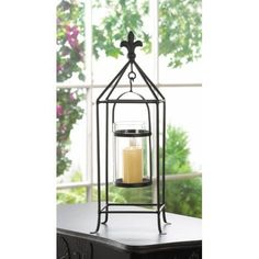 """Fleur De Lis Glass And Metal Candle Holder Decor. Ooh la la! Candlelight with a touch of European flair is a surefire way to amp up the style in your room. This Fleur De Lis Glass And Metal Candle Holder Decor features a black rod framework topped with a fleur-de-lis finial. Inside, a clear glass candle cup hangs from a simple metal frame that will let the light shine bright.   Item weight: 2 lbs. Iron and glass. Candle not included. 7"""" x 7"""" x 19"""" high; glass holder is 3 1/2"""" diameter x 5…"""