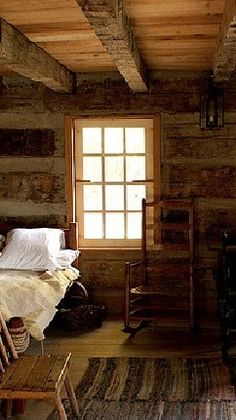 Rustic log cabin bedroom with old rocking chair.