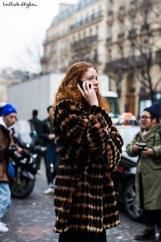 Street Style portraits by Ángel Robles. Fashion Photography from Paris Fashion Week. Redhead woman wearing and oversized coat after Maison Martin Margiela fashion show, Paris.