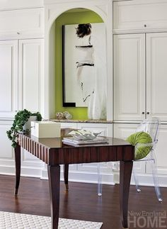Varying shades of green bedeck the curtains, chairs, coffee table and pillows, and the apple green of a small wall nook makes an abstract painting pop.