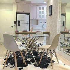 Sala de jantar com mesa em vidro. Cadeira Charles Eames branca, tapete de pele e armários brancos., papel de parede. Espelho lateral.
