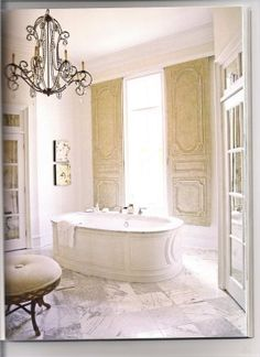 """This is a bath done by Amy Howard in her own home. I simply love her window treatment idea. She took antique doors and installed them like shutters on a sliding track. She concealed the track with decorative moulding."""