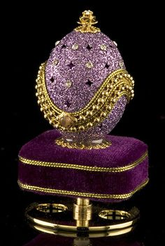 "Glittering lavender coats this authentic egg, which rests atop a pedestal covered with royal purple velvet. Star-shaped designs are cut into the egg shell, alternating with sparkling clear crystals. Golden beads and braid edge the lid, which opens to display a velvet-lined interior. Plays ""Shall We Dance"" as the egg rotates."