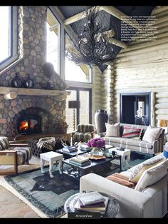 Furniture placement in a large room. Oversized ottoman in front of fireplace. Sand blasted light log walls with a brown painted ceiling. Good use of space with the spindly chandelier. Creative coffee table/stool arrangement.