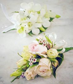 Love the bottom one!  Spray roses, Lisianthus, Waxfower. The other is a classic white Dendrobium orchid pin on corsage.