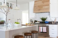 Beautiful kitchen features vintage white barn pendants illuminating a light gray shiplap center island fitted with a prep sink and vintage faucet lined with backless wood and iron counter stools.