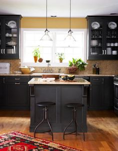 Gold-flecked granite tops black cabinetry in an Adirondack-style home's kitchen.  #kitchens