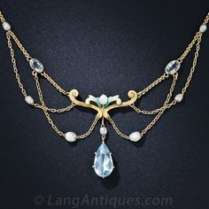 Circa 1900 - Pretty pastels, glistening gold and shimmering freshwater pearls combine to create this refreshingly feminine and consummate Art Nouveau necklace - circa 1900. The pear-shape aqua pendant is imbued with a serene light Caribbean-blue hue and the shaded enamel scrolls gradate from lime yellow to glacier blue. About 15 3/4 inches, sans pear-shape aqua.