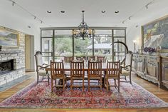 Dining room with a wall of windows, fireplace. Wood floors. Memorial Villages Houston TX Real Estate - 2210 South Piney Point Rd