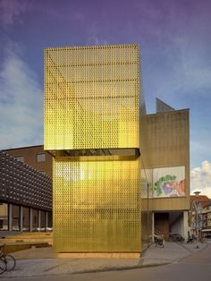 The perforated golden copper alloy facade panels of Switch+ by modulorbeat