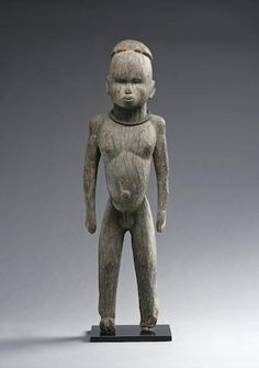 A superb Lobi figure Burkina Faso, of exceptional form, standing erect in hieratic posture, with variegated gray surface, rendered with an uncharacteristic strength and naturalism, iron collar about the neck.  height 32in
