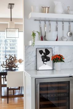 TheseFineWalls meets an Upper East Side apartment. White marble kitchen with black and white leaning framed Twiggy photo by Ulrich Knoblauch