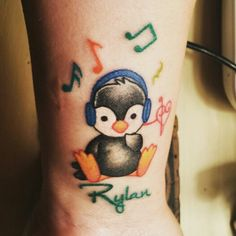 Penguin tattoo in memory of my son, Rylan. Penguin because he told me in a dream he wanted to hug a fluffy one, and penguins mate for life- and Rylan was my soul mate. Headphones and music notes because he LOVED his music and we rocked and sang every day. The colorfulness was bright, like his room, his memory quilt and yearbook page. I often called him a horse of a different color.