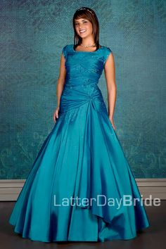 This modest prom dress of taffeta has a dropped waist and ball gown feel. With a wrapped bodice, scattered beading, and corset lacing in back