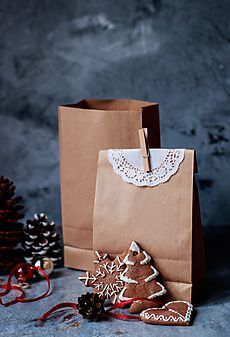 Brown paper bag with a christmas cookie by Babett Lupaneszku for Stocksy United