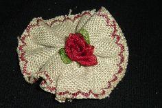 Flor en lino, rosita central y festón en granate