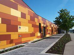 Bunte Fassadenverkleidung einer langen Mauer durch die Dach Schneider Weimar GmbH in Umpferstedt (99441) | Dachdecker.com