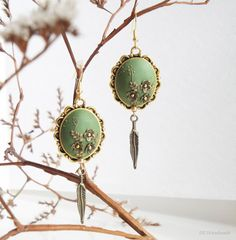 Asparagus green earrings with brass flowers decoration and bronze leaves on…