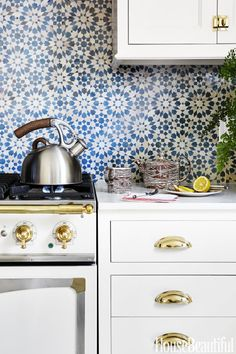 BLUE AND BRASS – In a Hudson Valley home, white cabinetry sets off a kitchen backsplash in Mosaic House's Batha Moroccan tile. The brass cabinet hardware harmonizes with details on the La Cornue range. Click through for the entire gallery and for more backsplash ideas.