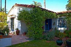 The Spanish Revival bungalow or casita has a red-tile roof and a courtyard patio on one side.