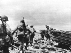 6 juin 1944. Une section qui vient de débarquer au Ruquet à Saint-Laurent-sur-Mer, longe sur les galets le rivage d'Omaha Beach, jonché de matériel abandonné. A droite, un DUKW 353.