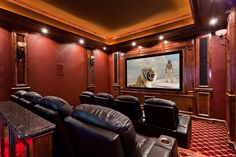 Beautiful, traditional red home theater conversion by Starlight Home Theater. Custom millwork, columns, sconces, carpet with lighting riser, tray ceiling with cove lighting. HD Projection with 7.1 surround sound system!