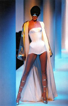 classicmugler:    Stella Tennant wears a gold satin robe lined with a white towelling over corseted swimsuit in white cotton piqué (Mr Pearl), with mirrored sunglasses and knee-high Greek sandals in gold leather.  Thierry Mugler'Les Colonnes'Prêt-à-Porter CollectionSpring Summer 1996Photo by Patrice Stable