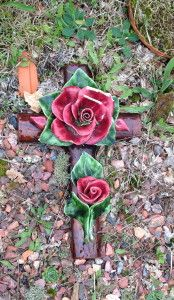 kruis met rode rozen van keramiek Franse bloemen van keramiek op een kruis op een begraafplaats in Nederland Augustus 2013 Cross decorated with ceramic flowers the Netherlands