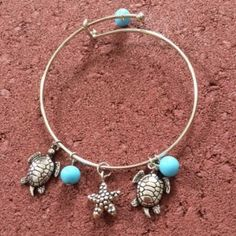 "Sea Life Silver Bangle Charm Bracelet Silver adjustable bangle bracelet with blue beads. Sea life charms include two turtles and a starfish. Turtle and starfish charms measure over 1/2"" each."