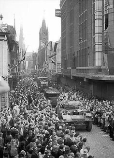 Daimler Armored Car and trucks passing through cheering crowds in Eindhoven, the Netherlands, 20 Sep 1944