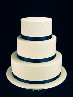 Quilted fondant wedding cake with edible pearls on chocolate mud cakes. Middle tier is white chocolate mud cake. Finished with navy blue ribbon. www.facebook.com/cakesbyleannerhodes