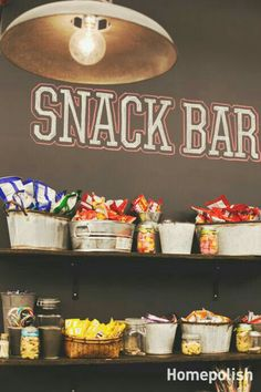 Snack bar using buckets and tins to put goodies in sitting on shelves for the kitchen walls