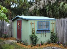 backyard shed makeover - My Repurposed Life™ don't like the colours but I like the window shelf and trelises.