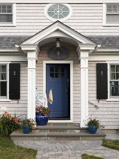 Framed by roof-supporting columns, this front door demanded notice. The homeowners referenced their coastal locale by painting the door a deep-sea blue that pops against the home's siding and trim. Vividly glazed containers and blue-toned pavers carry the door's hue further into the landscape.
