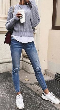 #fall #outfits women's gray stripe close-neck sweater, white shirt, whiskered blue washed fitted denim jeans, pair of white Adidas Superstar's, and brown leather chain-link shoulder bag outfit